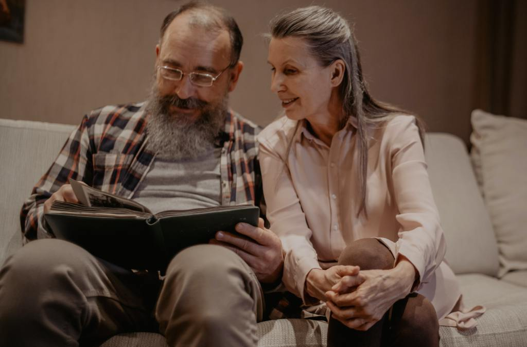 Two elderly people looking through a photo book.