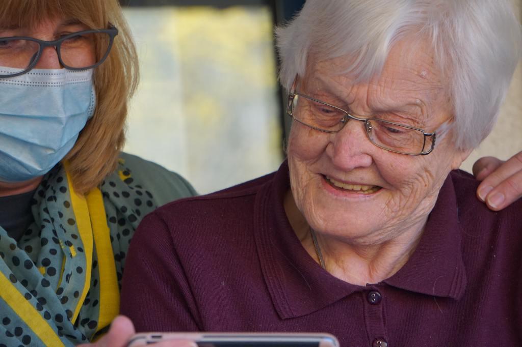 A woman showing an elderly woman a smart phone.